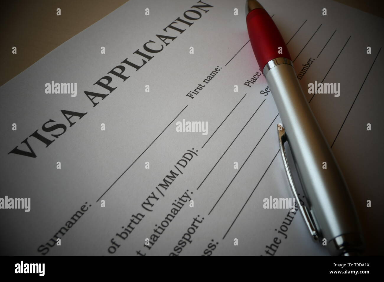 Visa application form with a pen for filling out. Document For applying to enter in a foreign country. - Stock Image