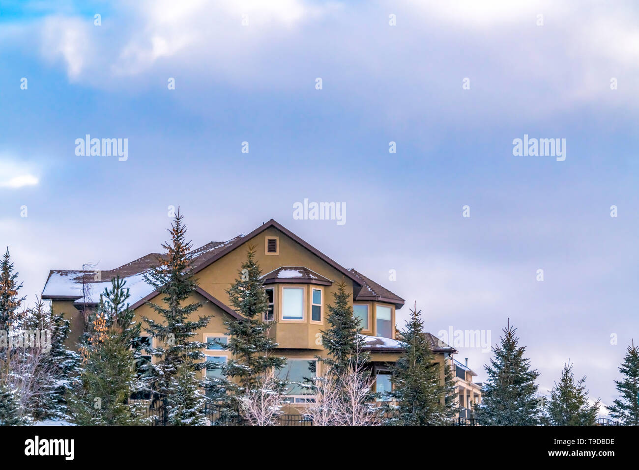 Exterior of an elegant house against blue sky with puffy clouds in winter - Stock Image
