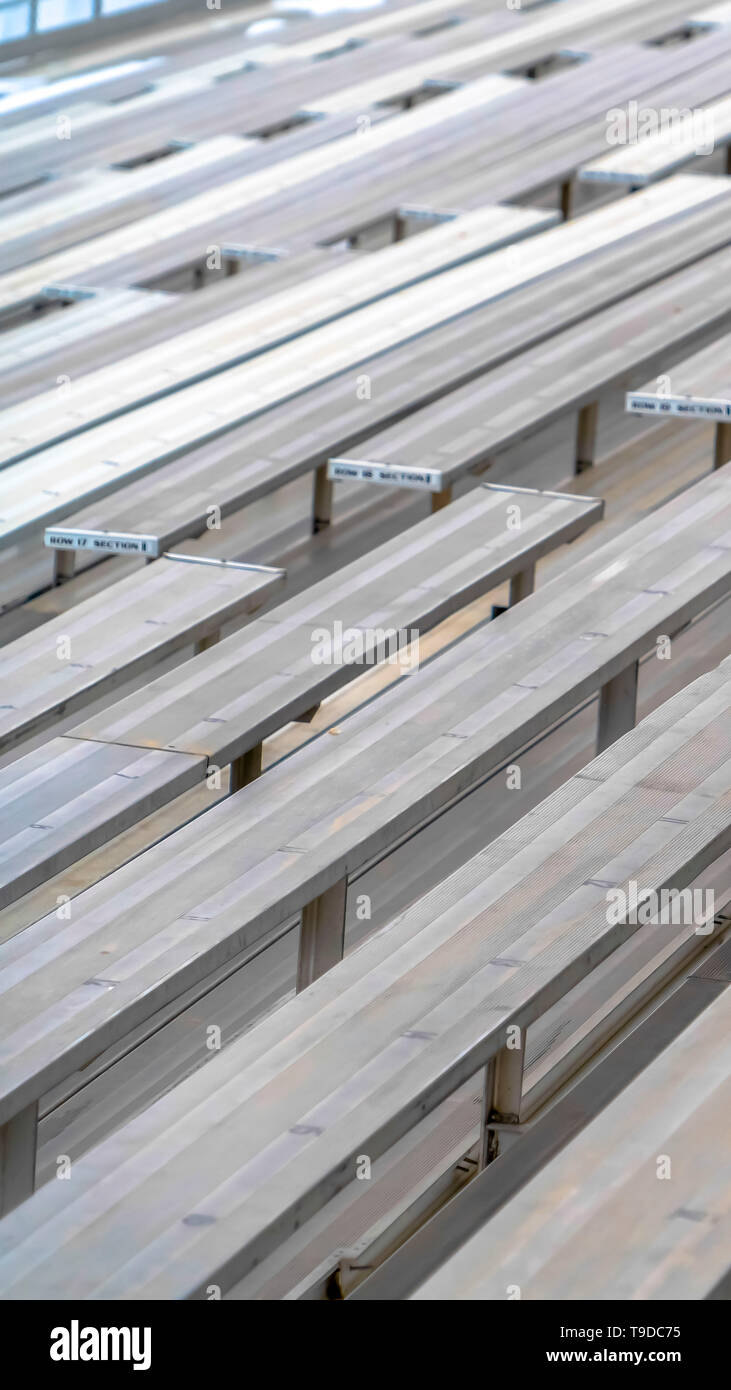 Vertical Close up of tiered rows of benches at a sports field viewed on a sunny day. - Stock Image