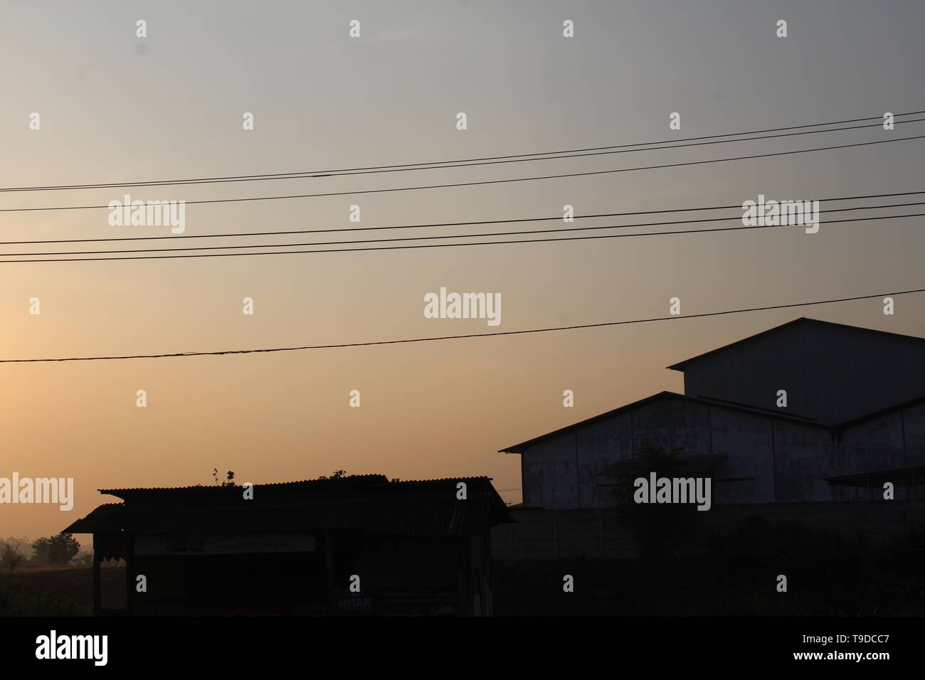 Sun rises behind the building. - Stock Image