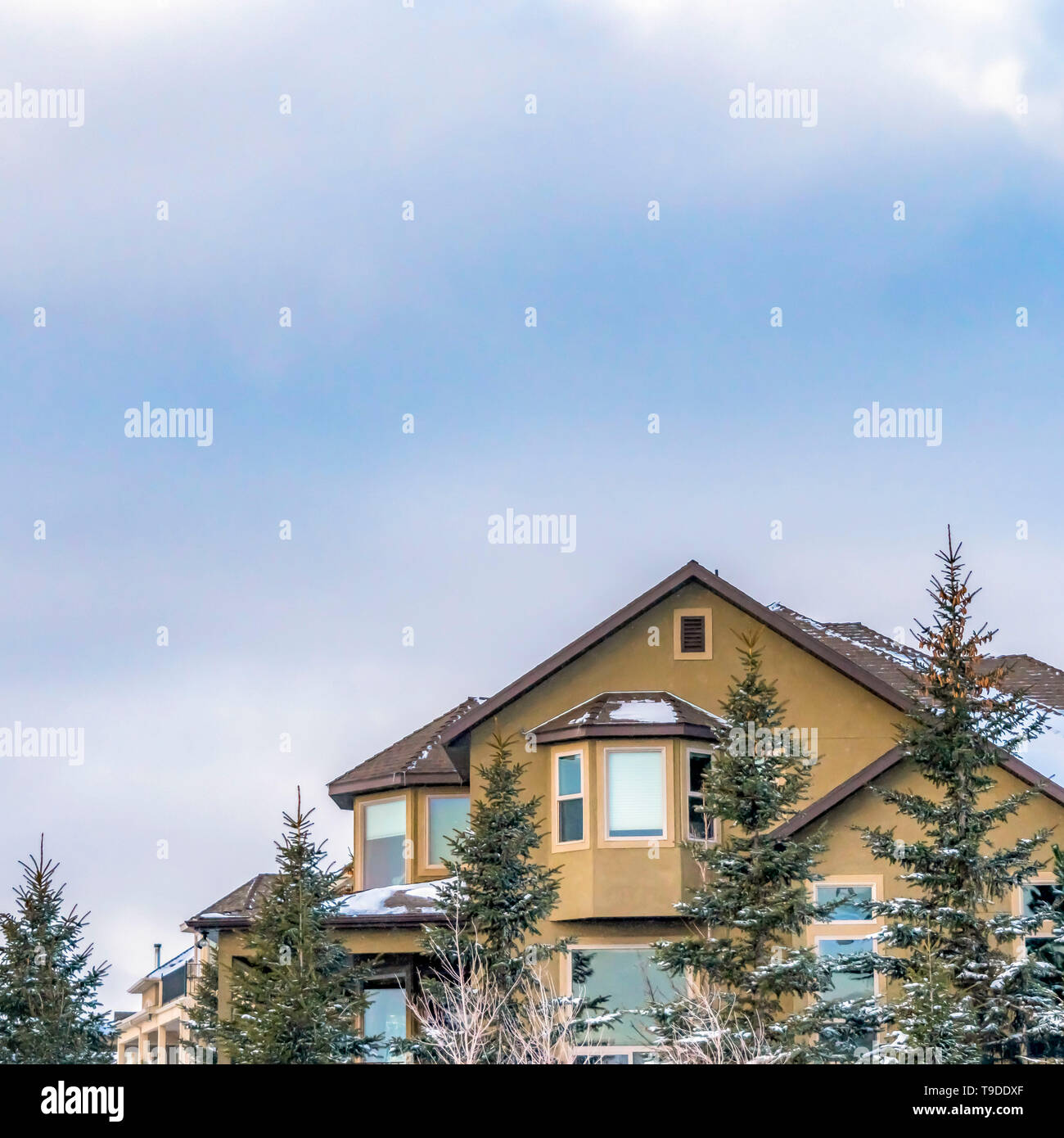 Clear Square Exterior of an elegant house against blue sky with puffy clouds in winter - Stock Image