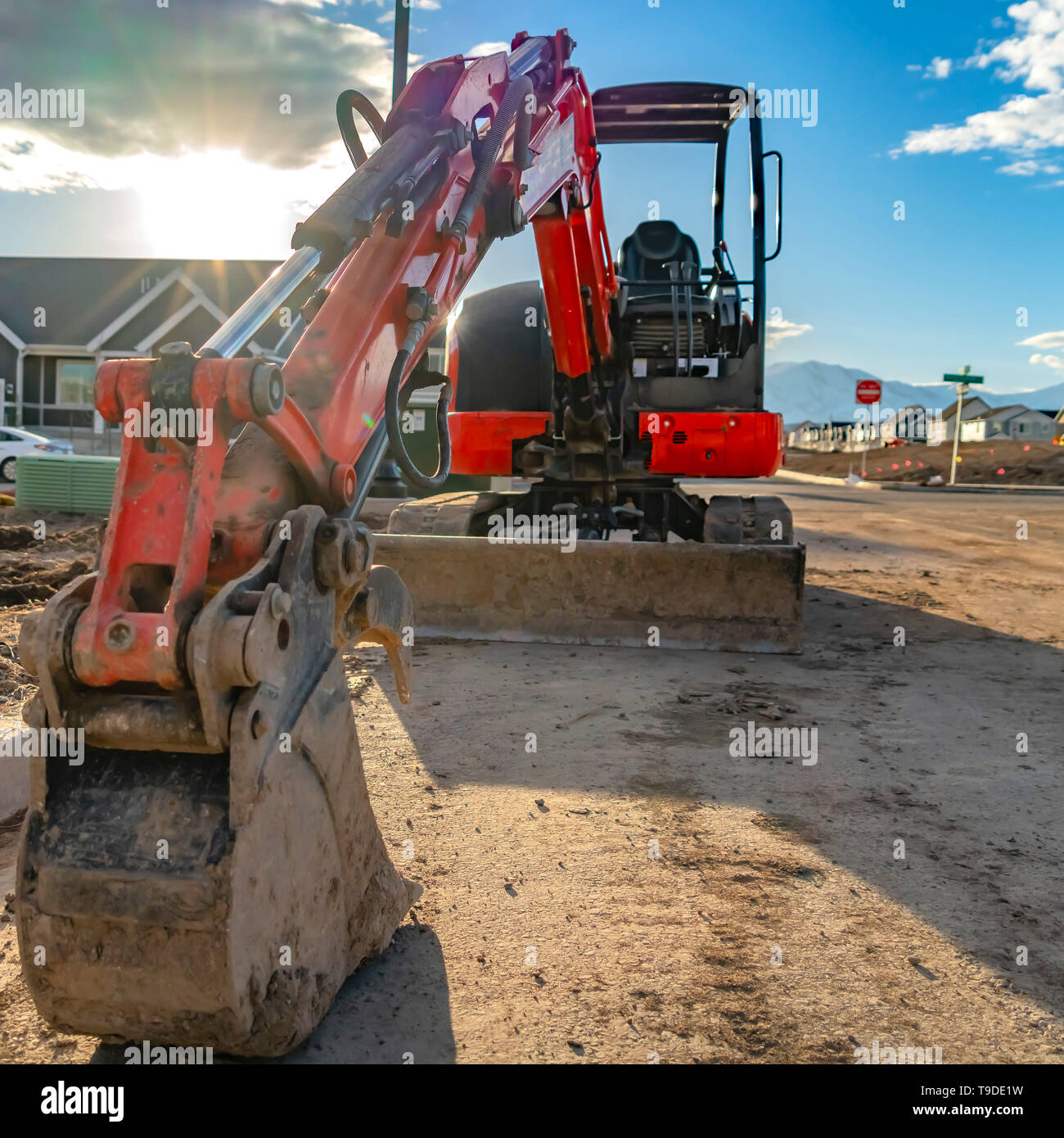 Square Close up of a red excavator with an attched grader blade viewed on a sunny day - Stock Image