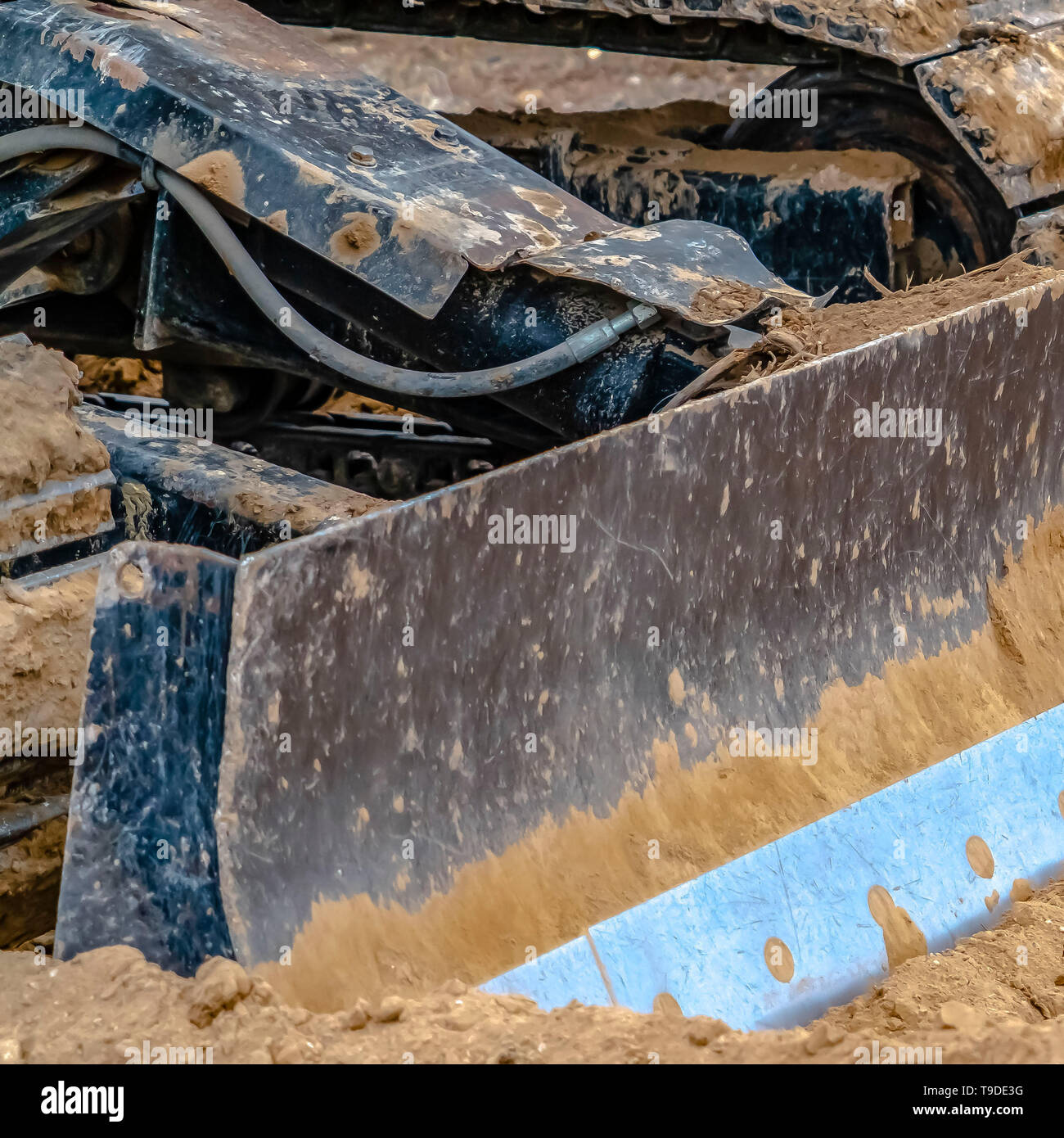 Square Close up of a metal grader blade against the ground with brown soil - Stock Image