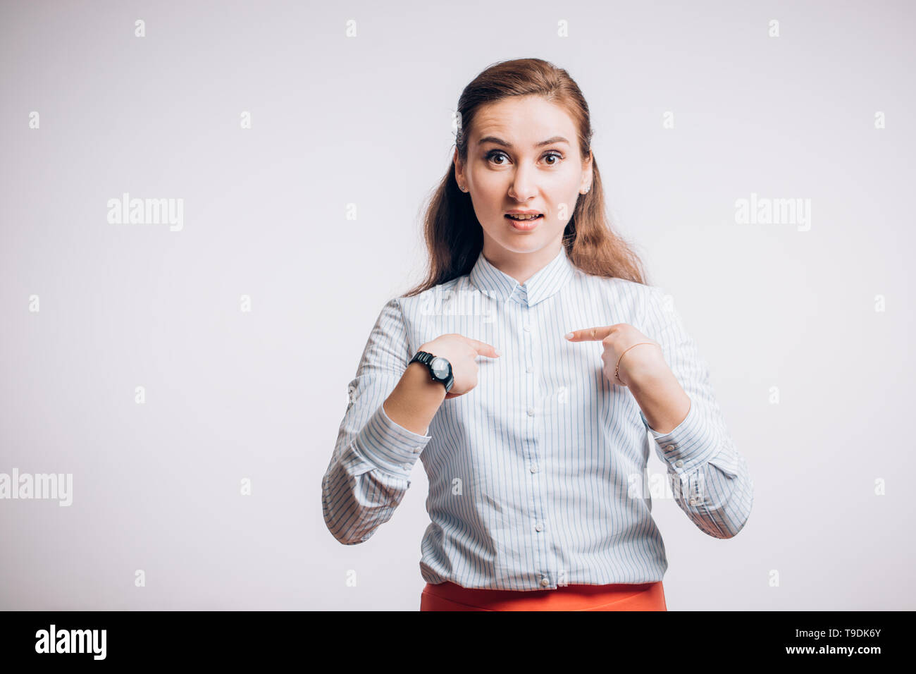 Young woman points at herself on white background, looks distrust. Business, success concept - Stock Image