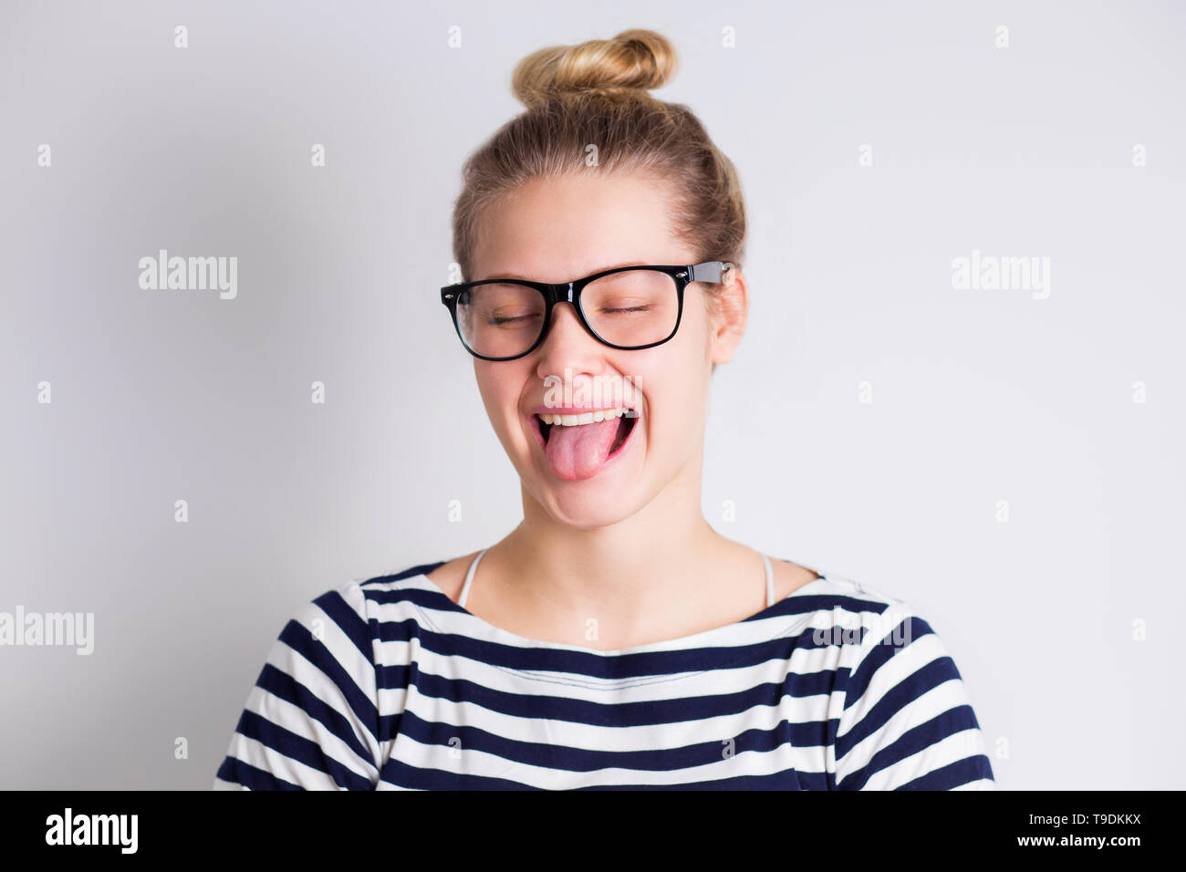 Crazy funny young blond woman in glasses showing tongue and smiling on white background. Positive emotions, facial expression, gestures concept - Stock Image
