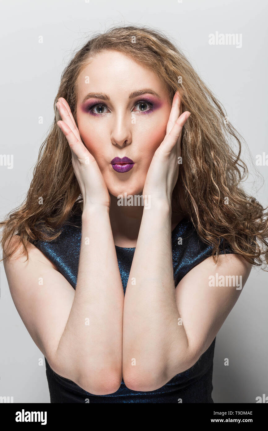 Surprise, bewilderment, emotions curly girl with bright makeup, hands on cheeks, closeup - Stock Image