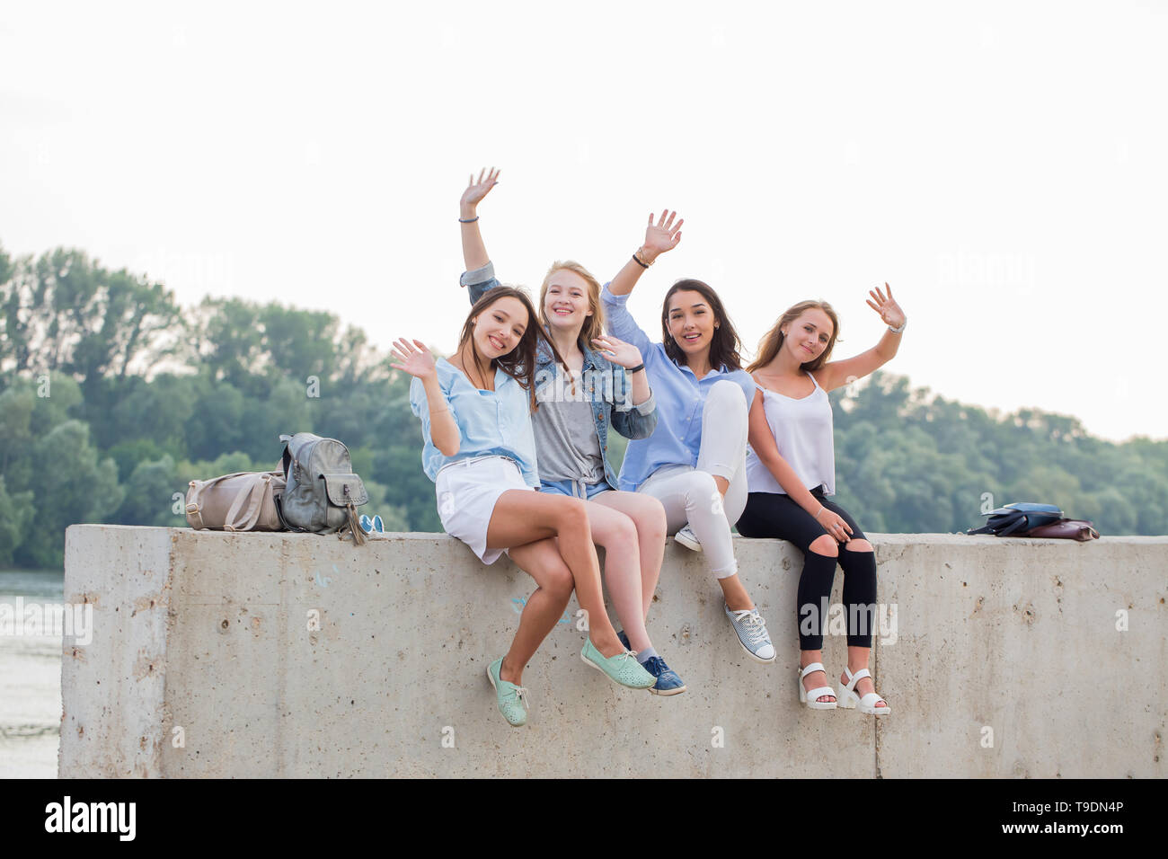 Happy female Friends Having Fun On Weekend, On Picnic Outdoors. Young Smiling People Sitting on concrete border and looking at camera - Stock Image