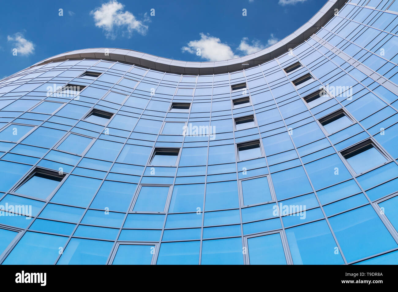 Blue glass tall building against the sky with clouds, view from below - Stock Image