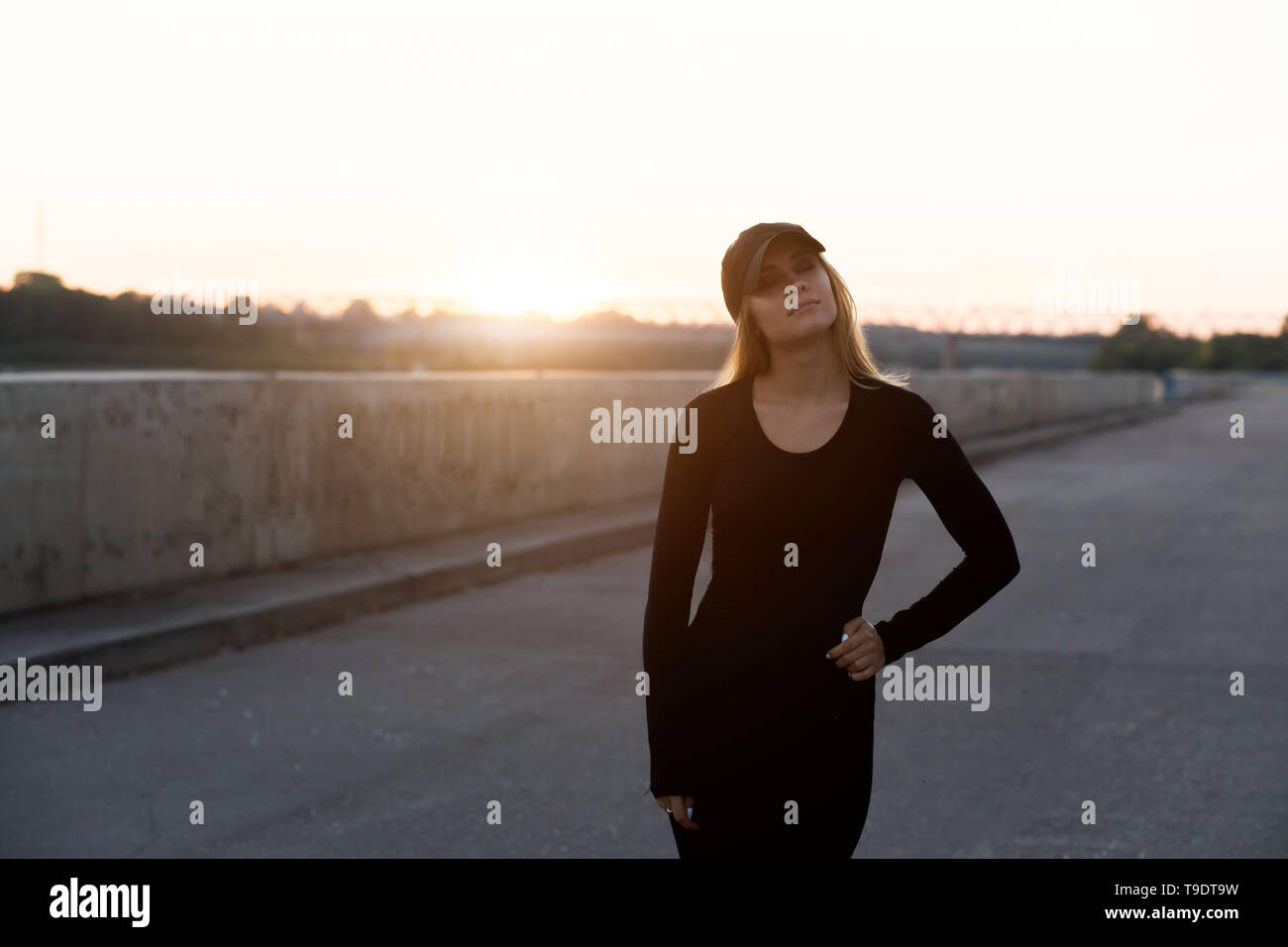 Beautiful young woman in black sports clothes and cap at sunset in the evening - Stock Image