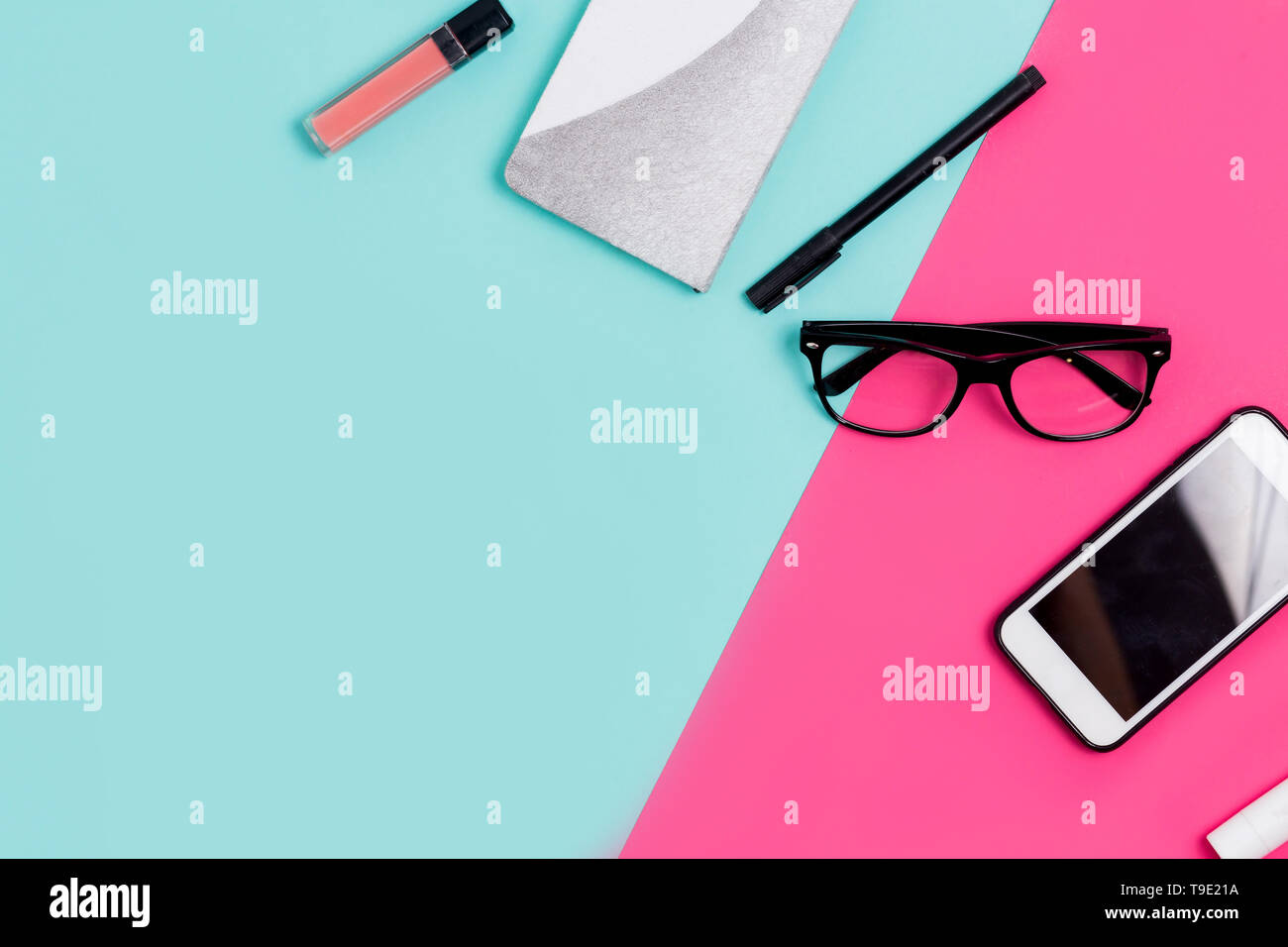 Flat lay traveler and office accessories on a colored background with copy space. Notebook, smartphone, glasses, pen, lipstick, lip gloss on the table Stock Photo