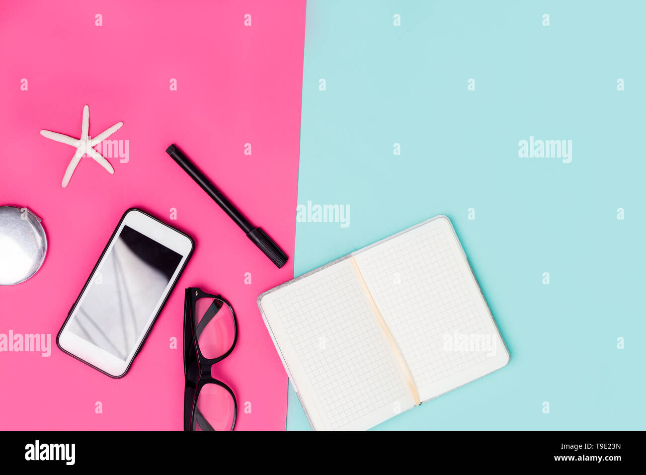 Close up office desk with stationery, glasses and smartphone. Spring pink and pastel blue background with womens work accessories - Stock Image