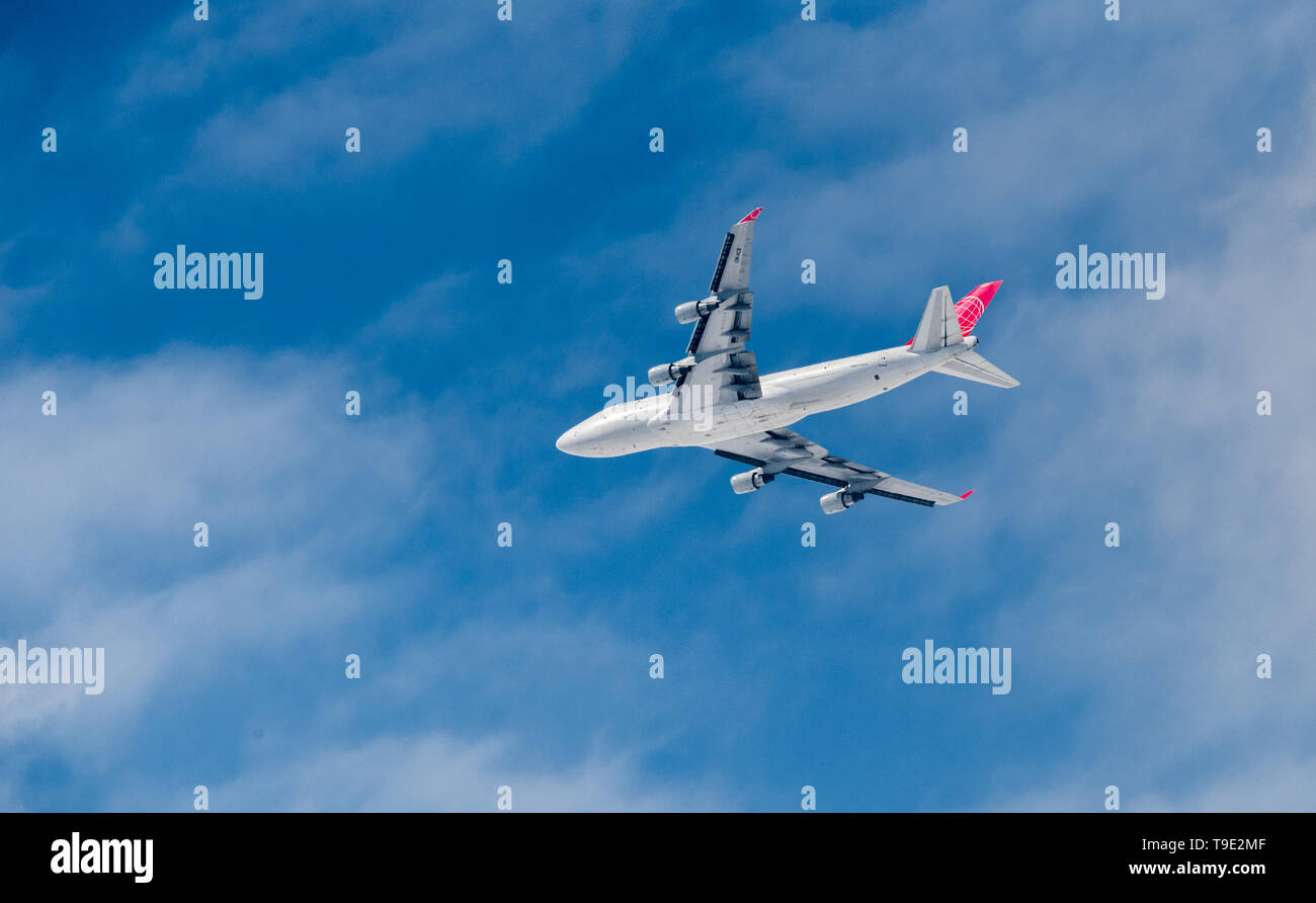 Air Cargo Global Boeing 747-433, OM - ACB cargo plane flying low through clouds. - Stock Image