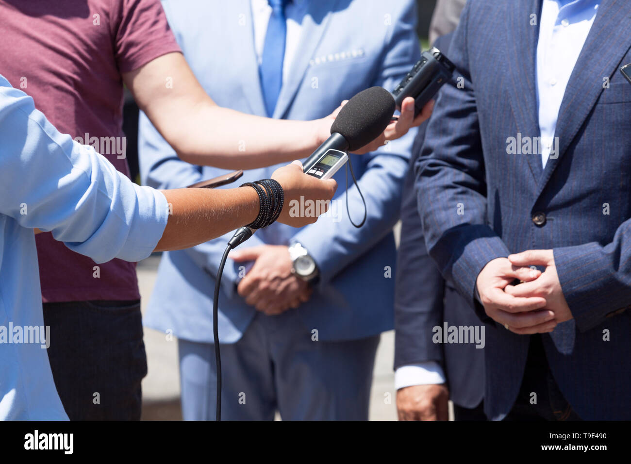 Journalists making media interview with unrecognizable business person or politician - Stock Image