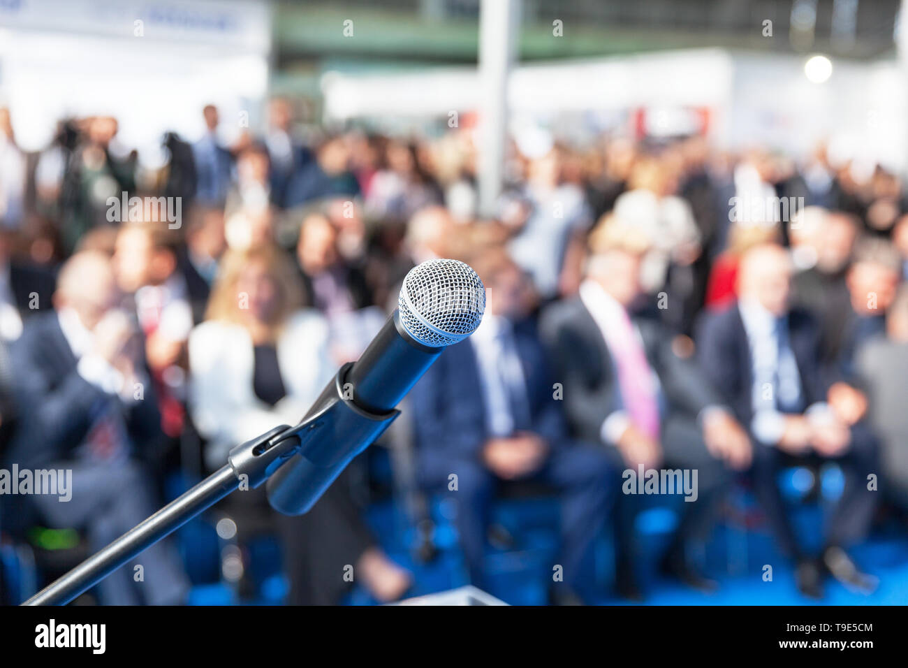 Microphone in focus against blurred audience - Stock Image