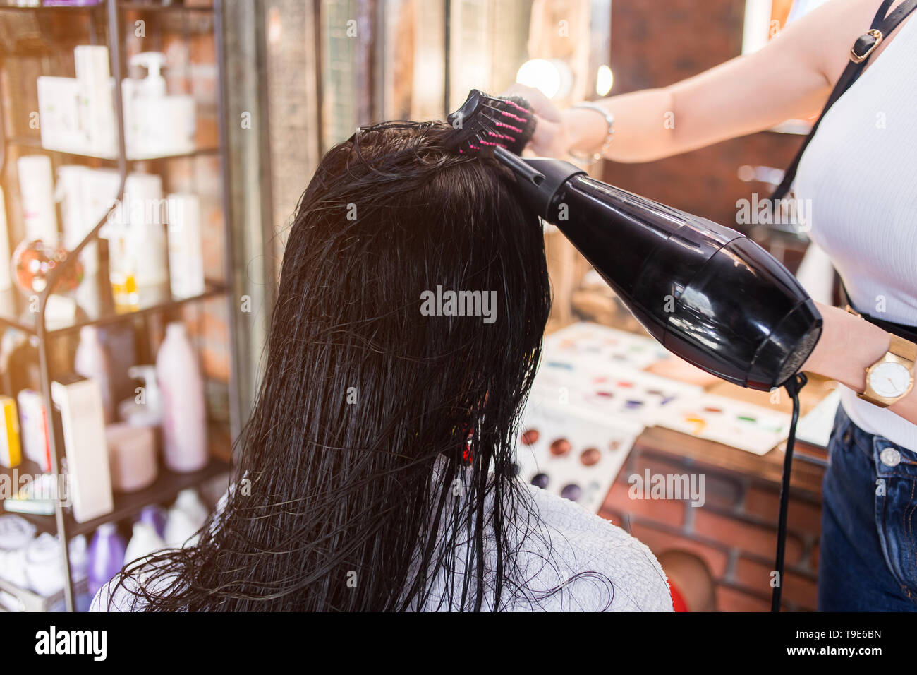 Beautiful brunette young woman at the hairdresser salon. Hairdresser making hairstyle. - Stock Image