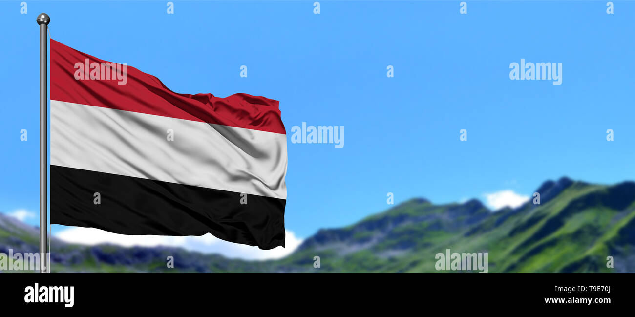 Yemen flag waving in the blue sky with green fields at mountain peak background. Nature theme. - Stock Image