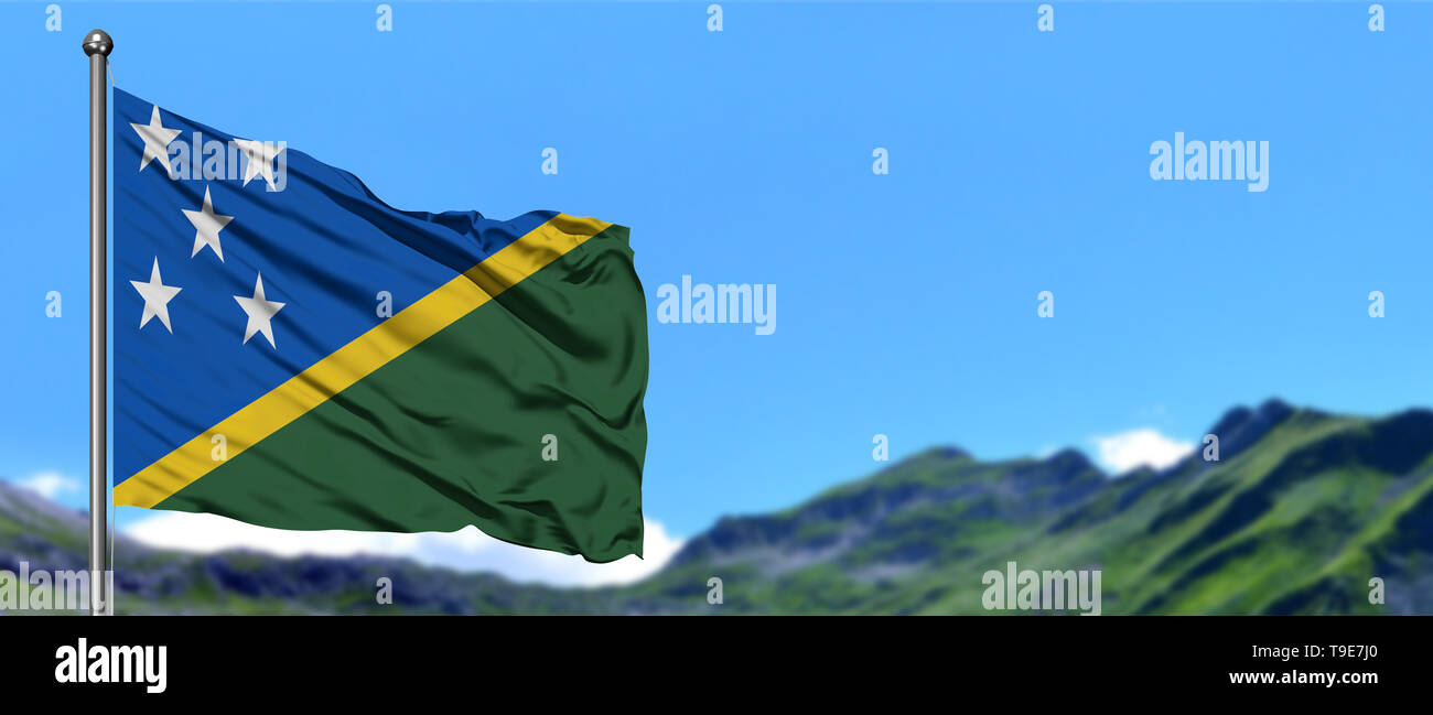 Solomon Islands flag waving in the blue sky with green fields at mountain peak background. Nature theme. - Stock Image