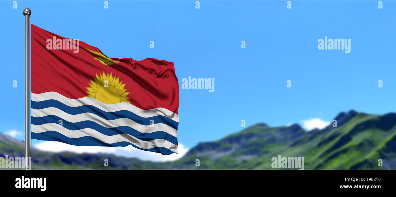 Kiribati flag waving in the blue sky with green fields at mountain peak background. Nature theme. - Stock Image