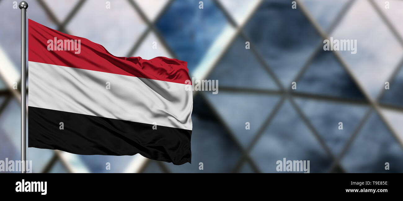 Yemen flag waving in the wind against blurred modern building. Business concept. National cooperation theme. - Stock Image