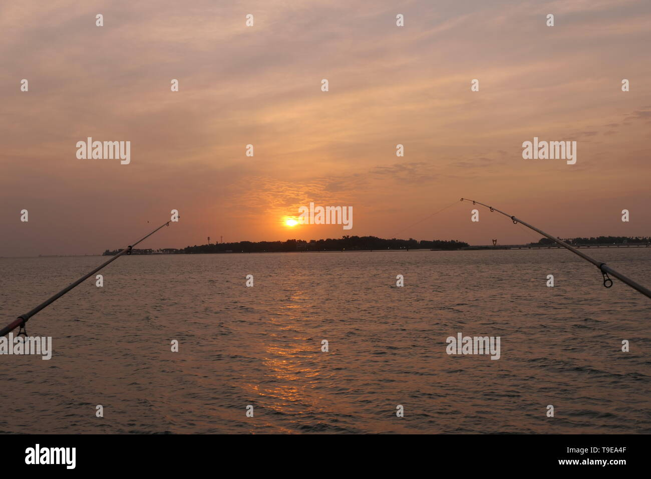 Natural and beautiful sunset with clear clouds and fishing rods in the background, at the coast of Jeddah, Saudi Arabia - Stock Image