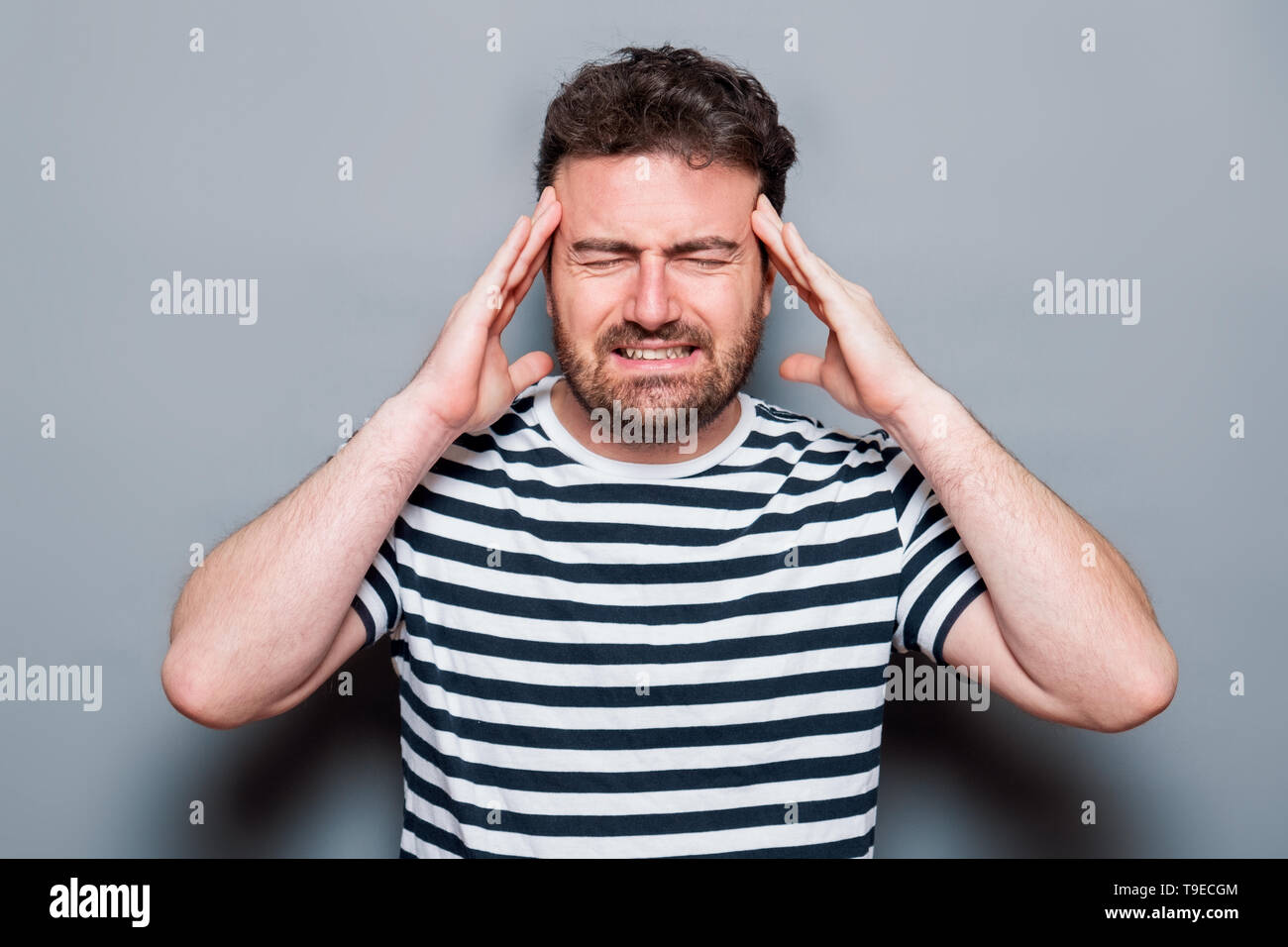 Studio portrait of headache caucasian male - Stock Image