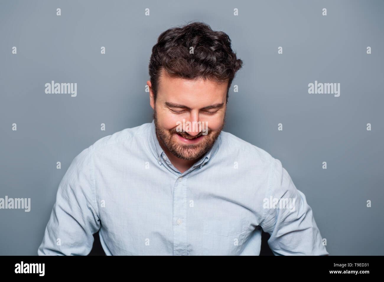 Studio portrait of laughing caucasian male - Stock Image