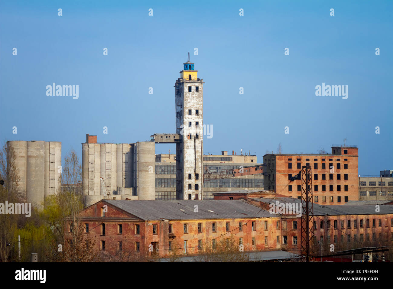 Abandoned damaged old granary against town and blue cloudy sky. - Stock Image