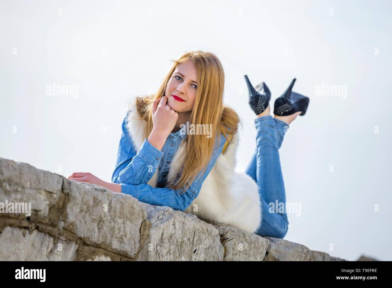 Teen girl crossed-legs Black heels pumps trousers - Stock Image