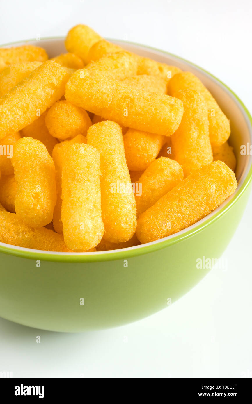 Cheese flavored puffed corn snacks in a bowl - Stock Image
