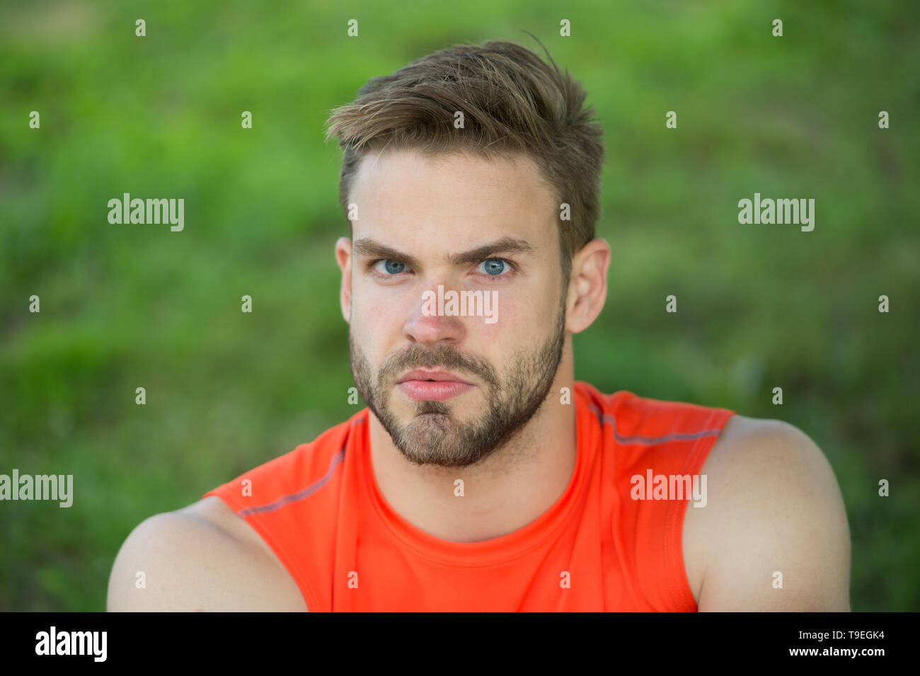 Taking minute break. Runner relaxing in shadow. Man with bristle strict face, grass background. Man unshaven looks handsome and cool. Guy bearded and  - Stock Image