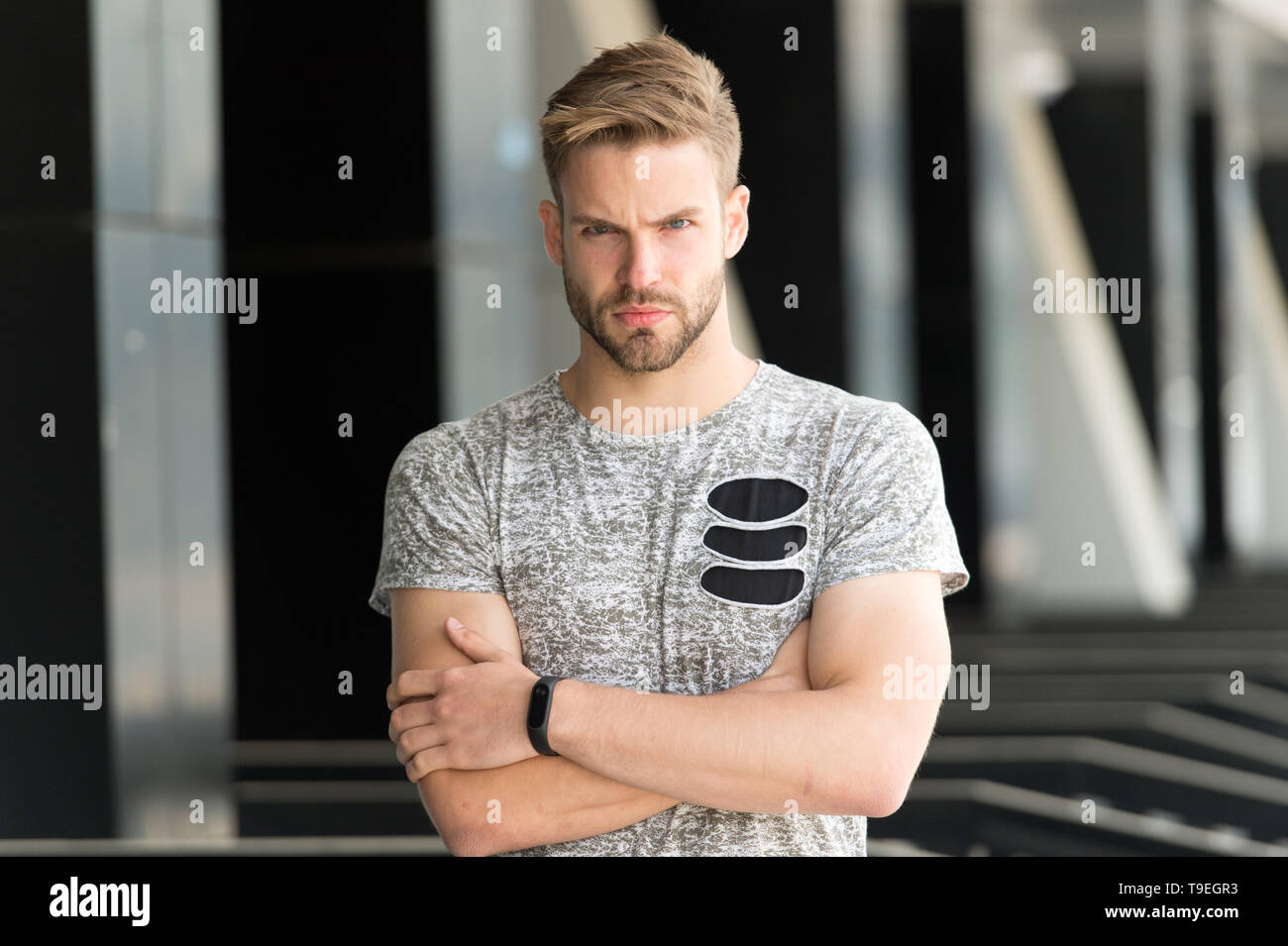 Man bristle serious face muscular shoulders, urban background, defocused. Man beard unshaven guy looks handsome and cool. Metrosexual concept. Guy bea - Stock Image