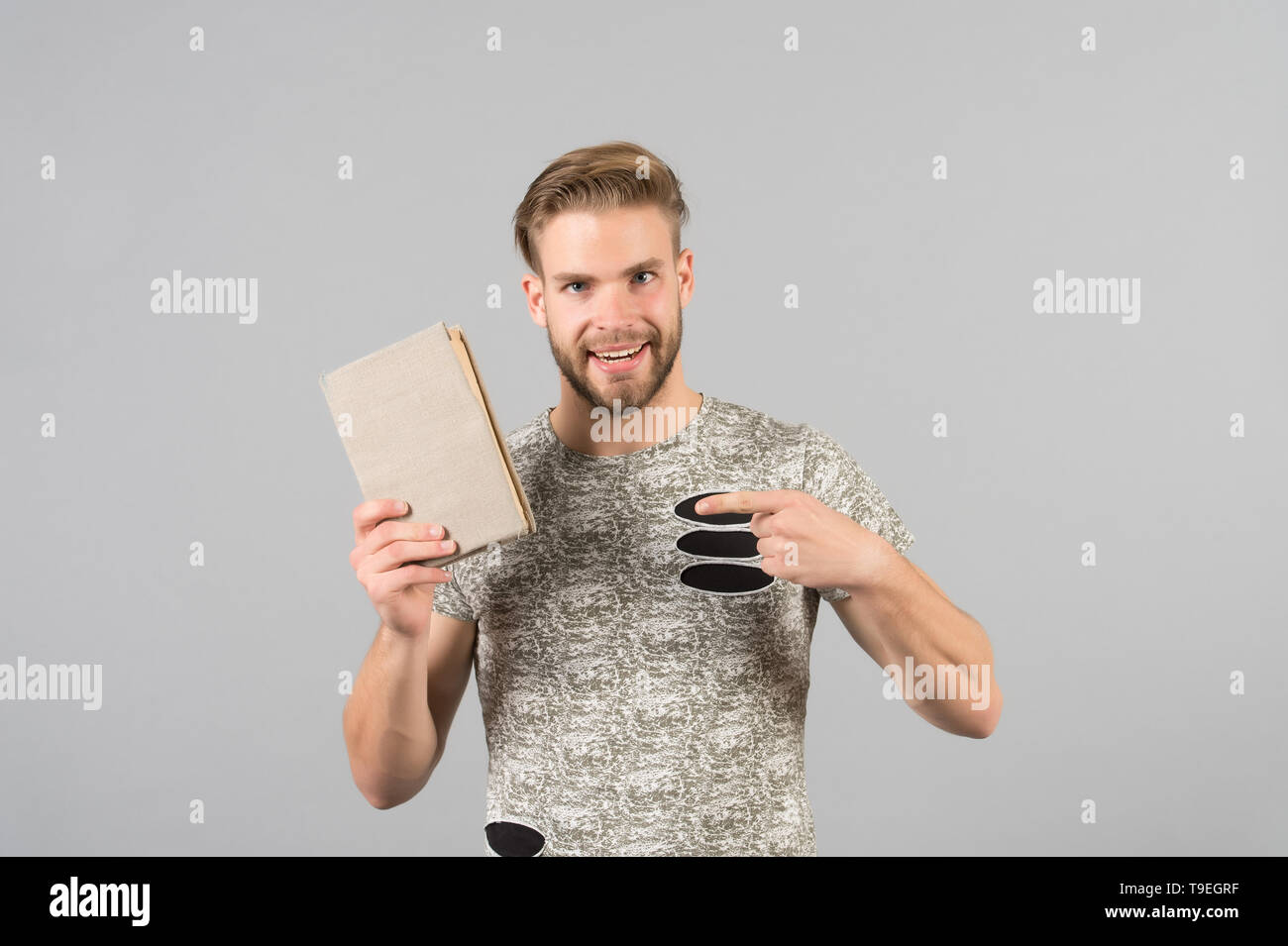Man bearded unshaven guy in stylish shirt pointing at book. Man smiling face recommends book, grey background. Literature recommendation concept. Man  - Stock Image