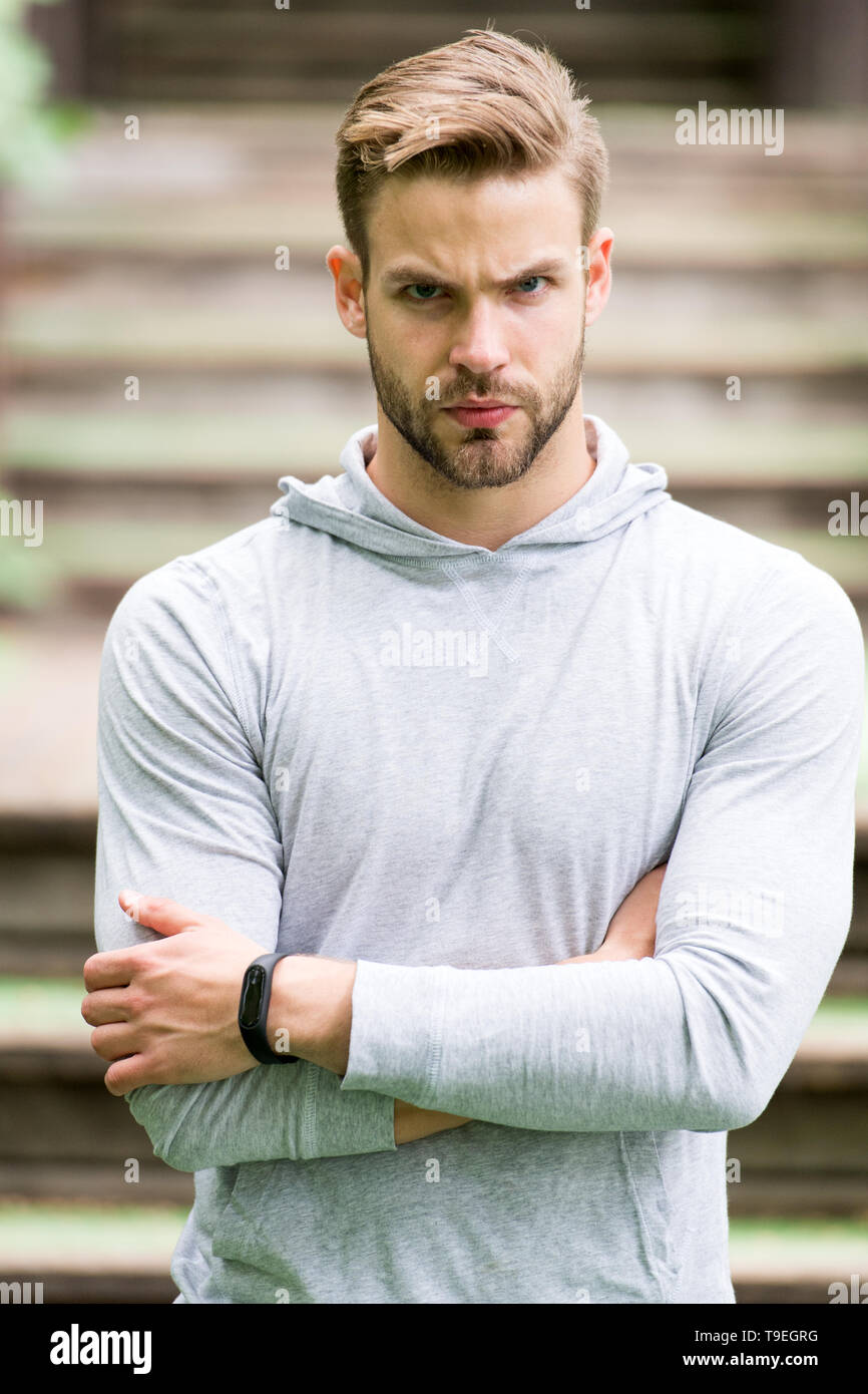 Handsome in style. Man unshaven folded arms looks handsome and cool. Guy bearded attractive cares about appearance. Man bristle serious face, urban ba - Stock Image