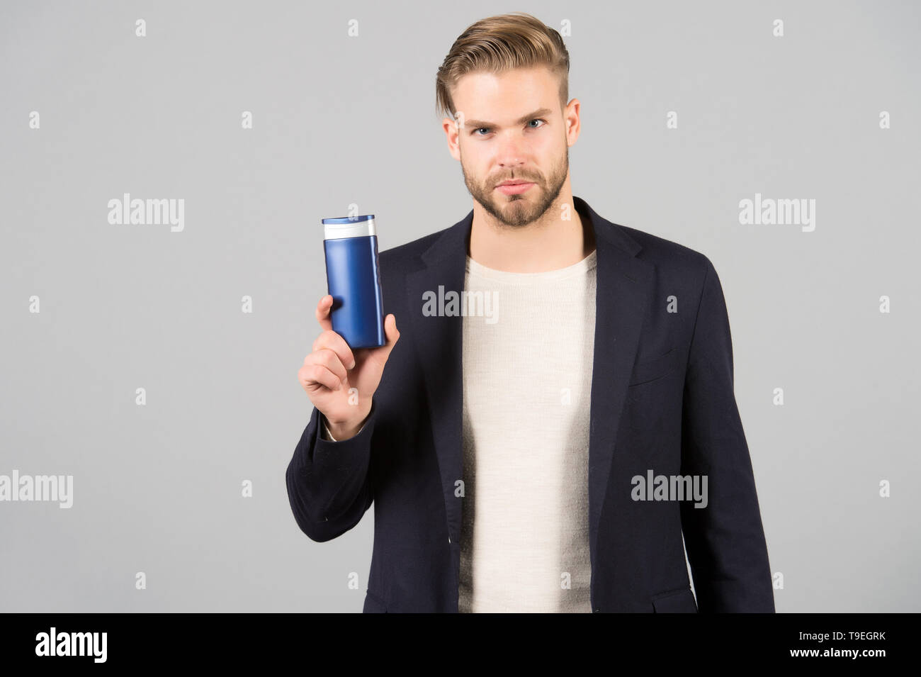 Man confident face holds shampoo bottle, grey background. Guy with bristle holds bottle shampoo, copy space. Man enjoy freshness after washing hair wi - Stock Image