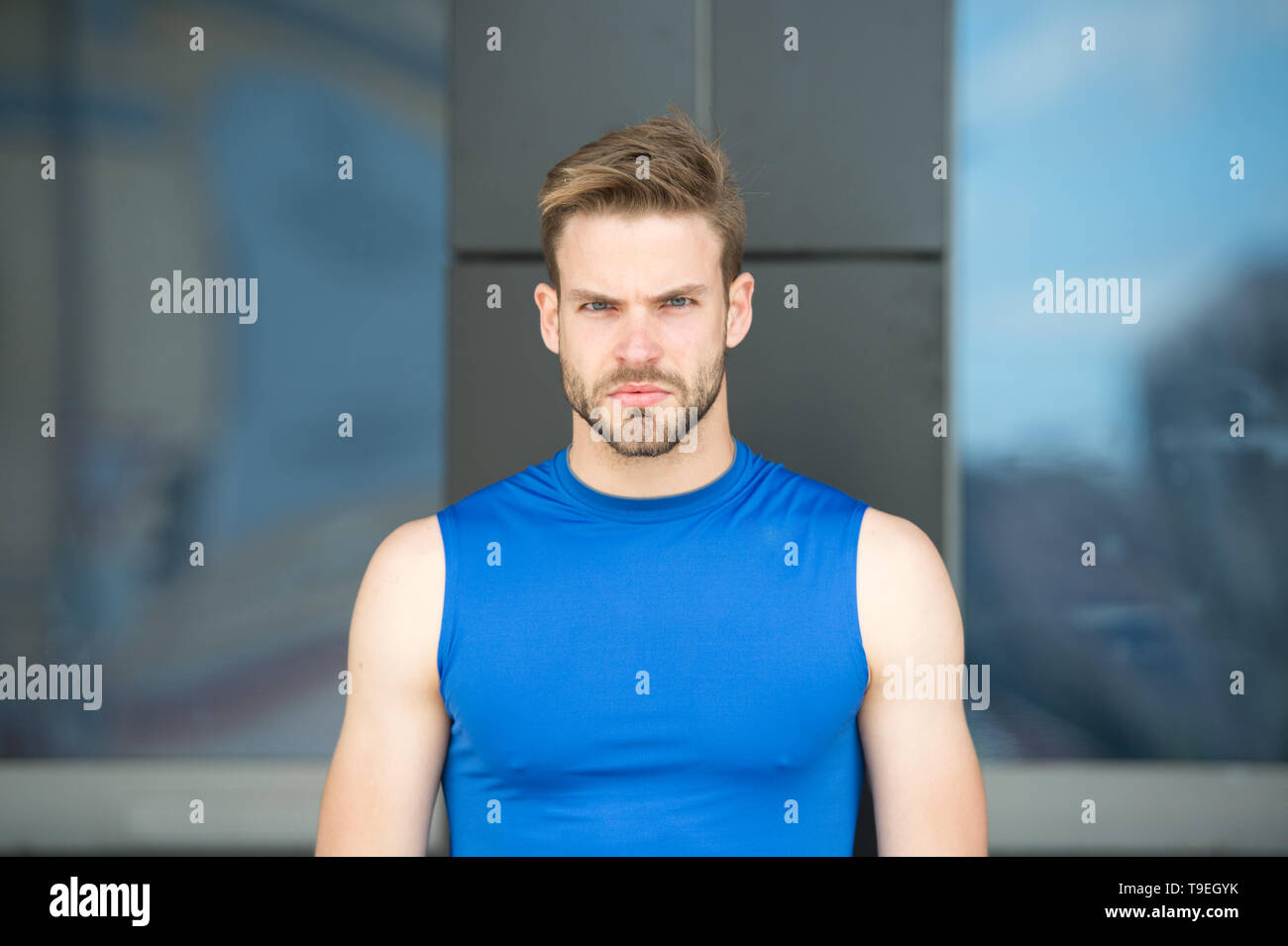 Man bristle serious face muscular shoulders, urban background, defocused. Metrosexual concept. Guy bearded and attractive cares about appearance. Man  - Stock Image