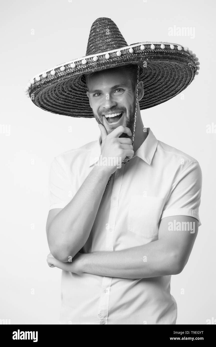 Festive time. Man on smiling face in sombrero hat thinks about party, light background. Guy with bristle looks festive in sombrero. Fest and holiday c - Stock Image