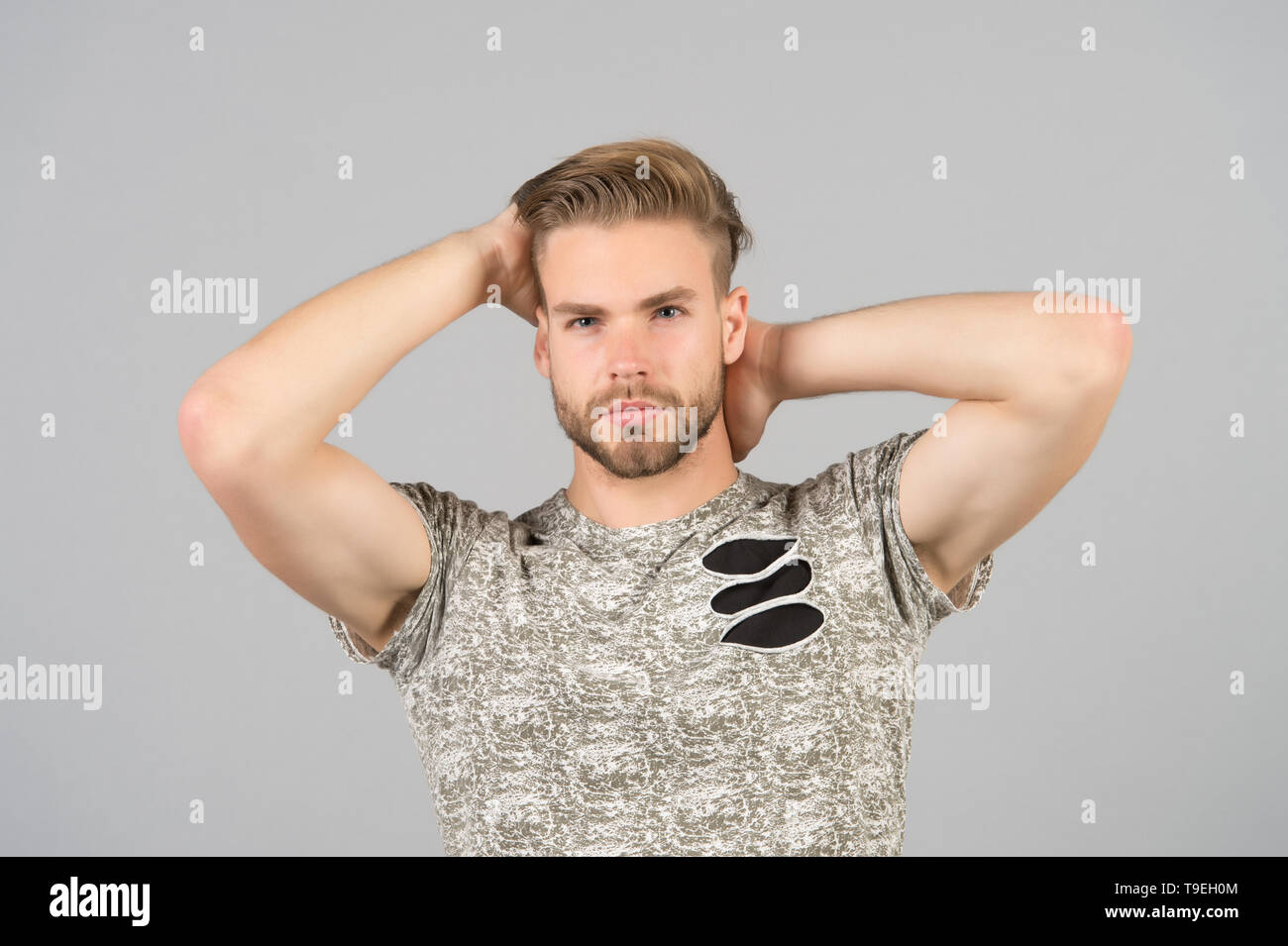 Guy bearded attractive with hairstyle. Man bearded strict face enjoy freshness of hair, grey background. Haircare concept. Man with beard unshaven guy - Stock Image