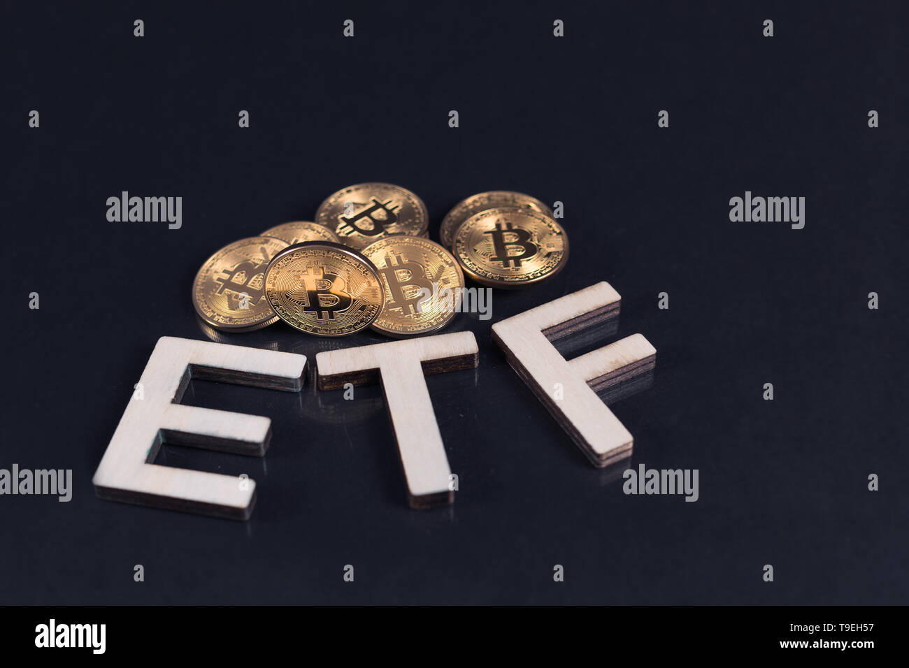 Bitcoin coins with ETF text put on dark background, Concept of the approval of Exchange Traded Fund. Stock Photo