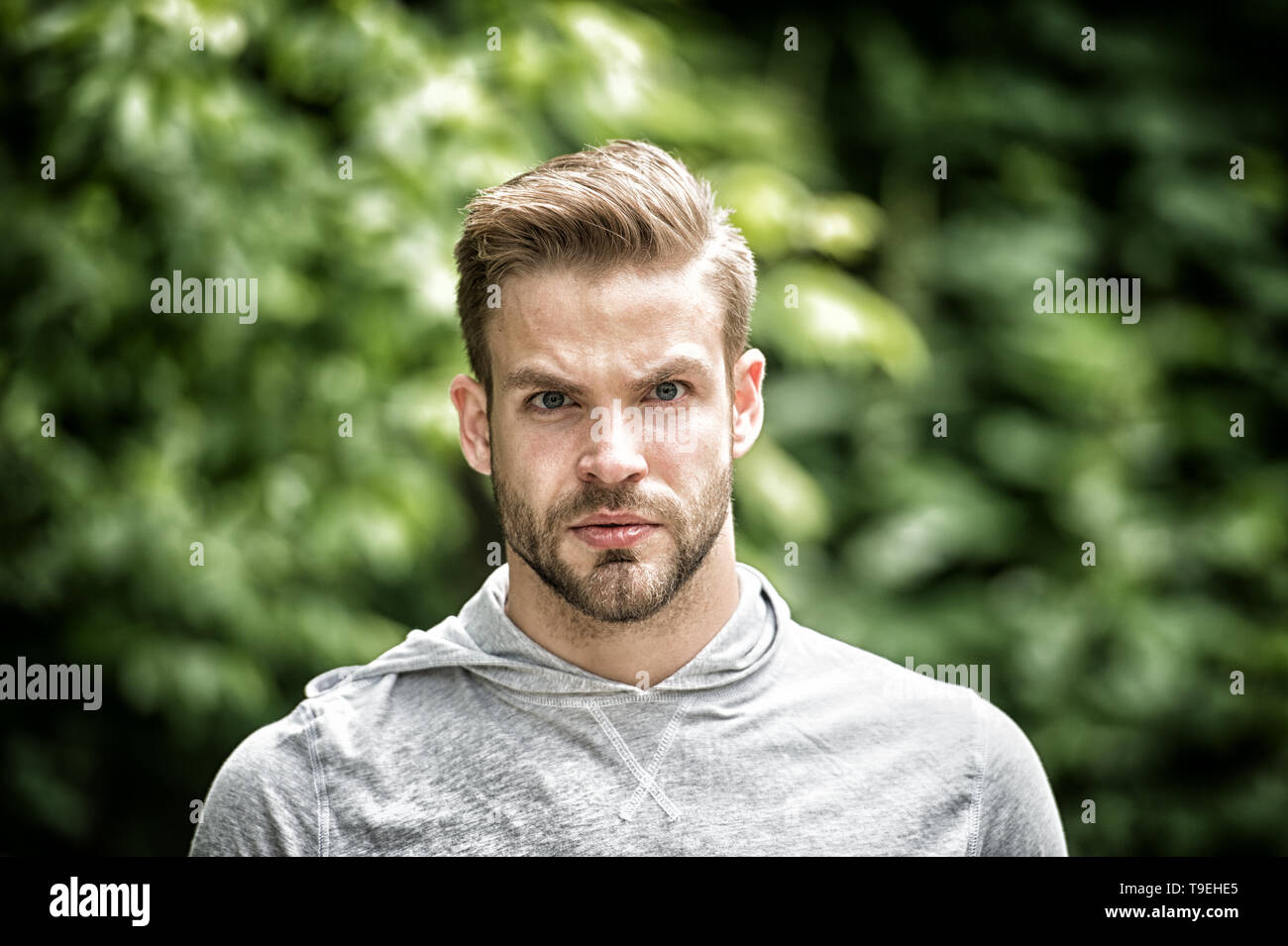 Handsome in style. Guy bearded attractive cares about appearance. Man bristle serious face, green nature background, defocused. Metrosexual concept. M - Stock Image
