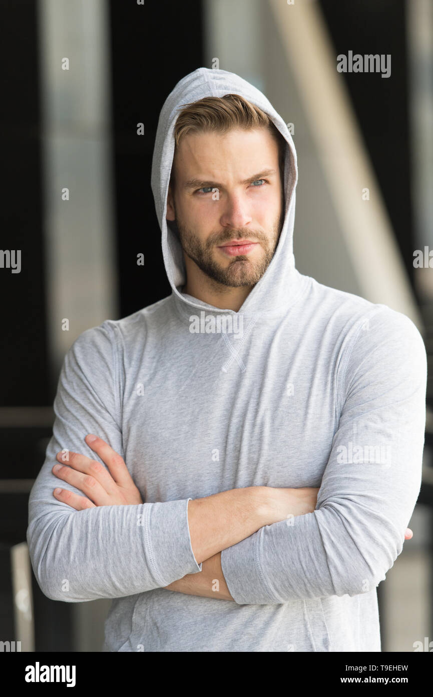 Cool and confident. Man unshaven hooded folded arms looks handsome and cool. Guy bearded attractive cares about appearance. Man bristle serious face,  - Stock Image