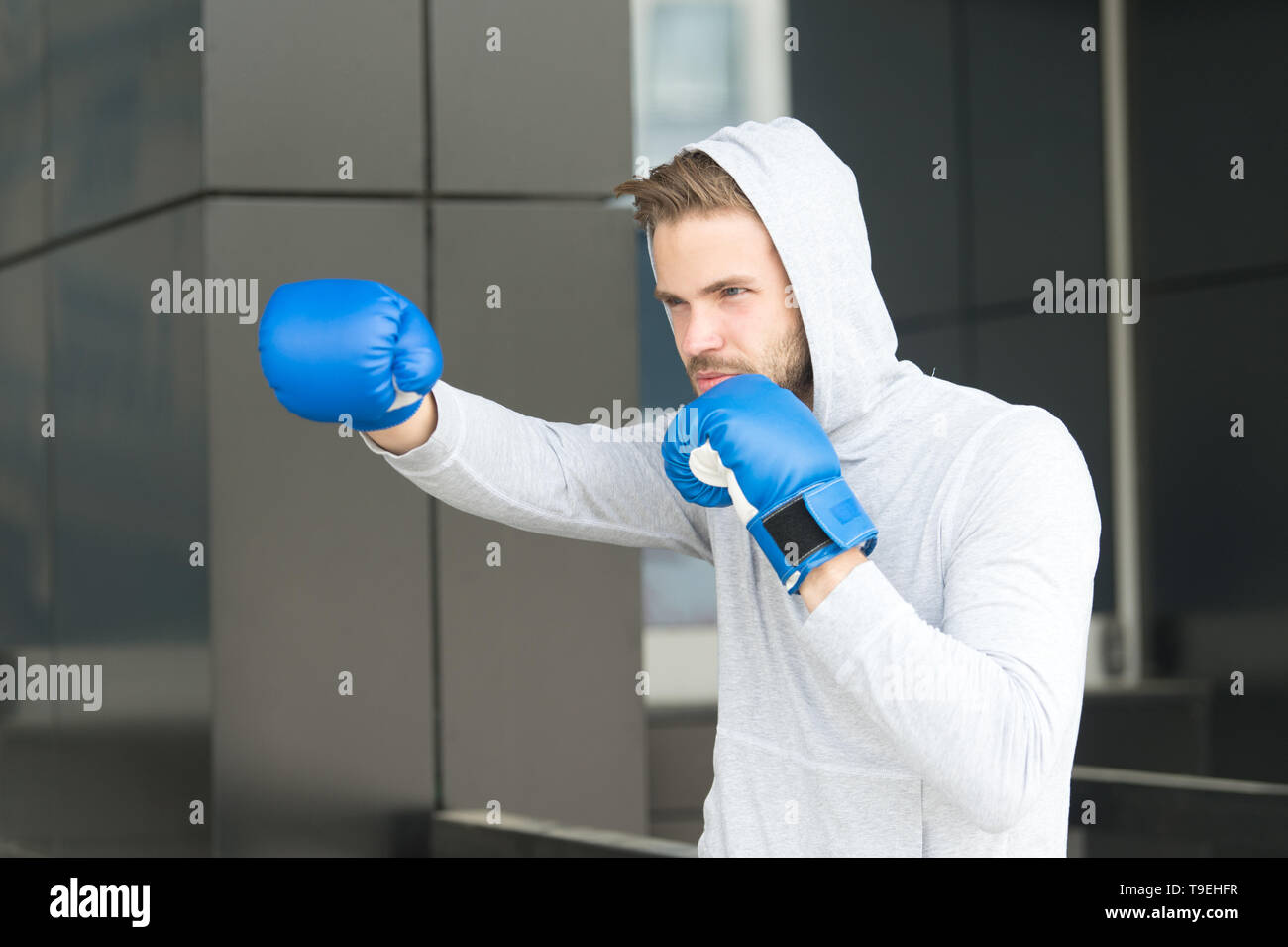 Man athlete on concentrated face with sport gloves practicing boxing
