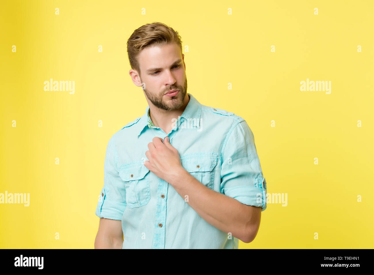 Man looks attractive casual linen blue shirt. Guy bristle undress casual shirt. Fashion concept. Man calm serious face confidently unbuttoning shirts  - Stock Image