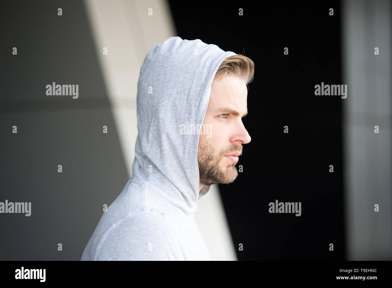 Guy bearded and attractive hooded, side view Man with bristle serious face, urban background, defocused. Needs to stay alone. Man beard unshaven guy l - Stock Image