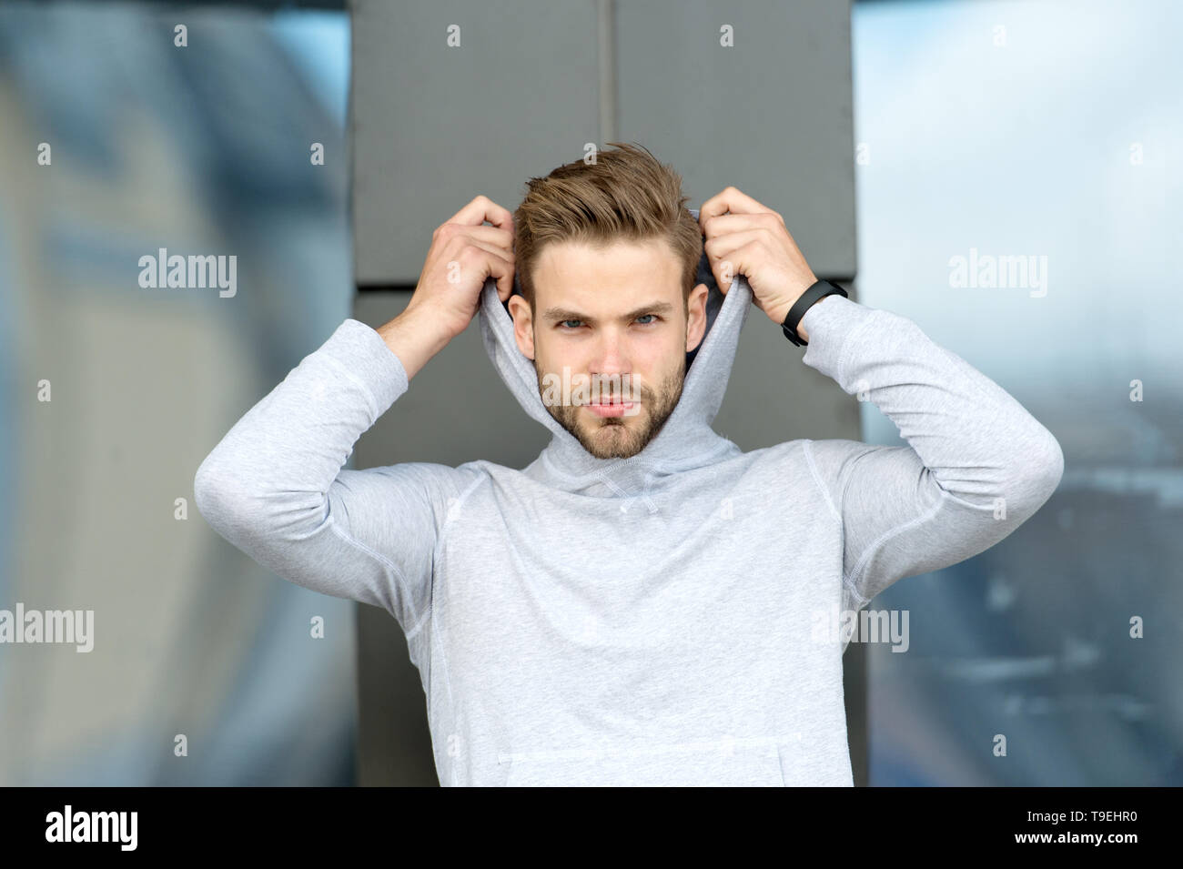 Feeling casual. Guy bearded attractive casual hooded. Man with bristle serious face, urban background, defocused. Man unshaven guy looks handsome casu - Stock Image
