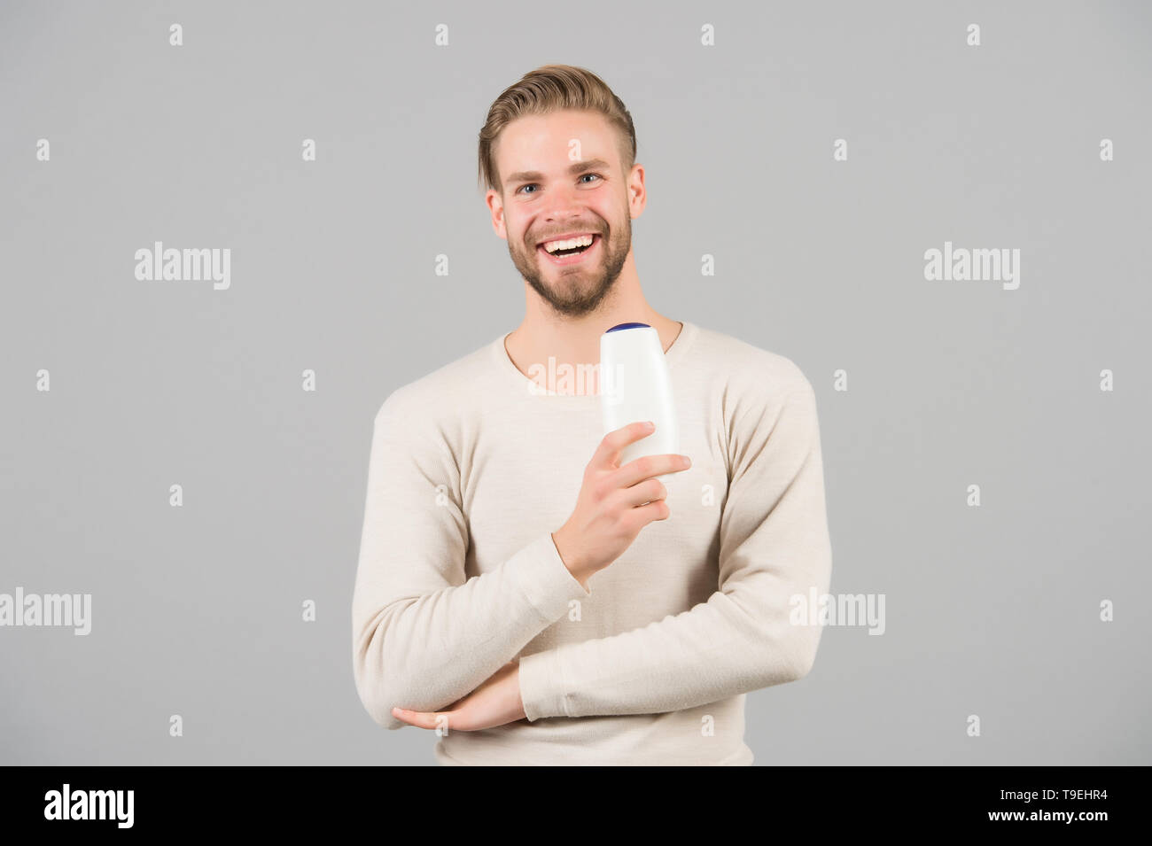 Hair care and beauty supplies concept. Man happy face holds shampoo bottle, grey background. Guy with bristle holds bottle shampoo, copy space. Man en - Stock Image