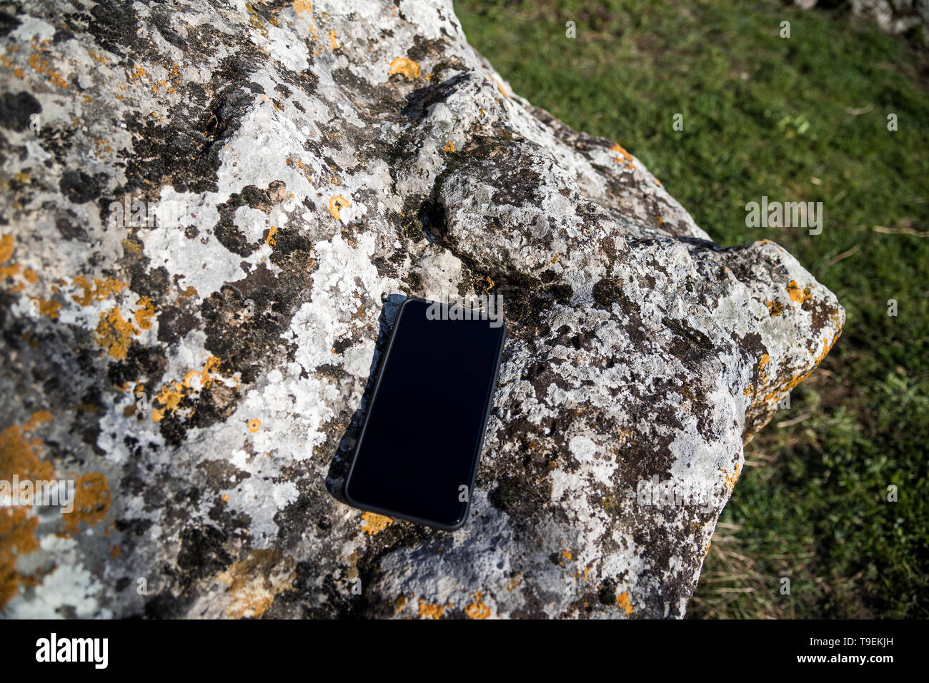 Black smartphone Apple iPhone Xs Max is lying on a rock in the sun Stock Photo