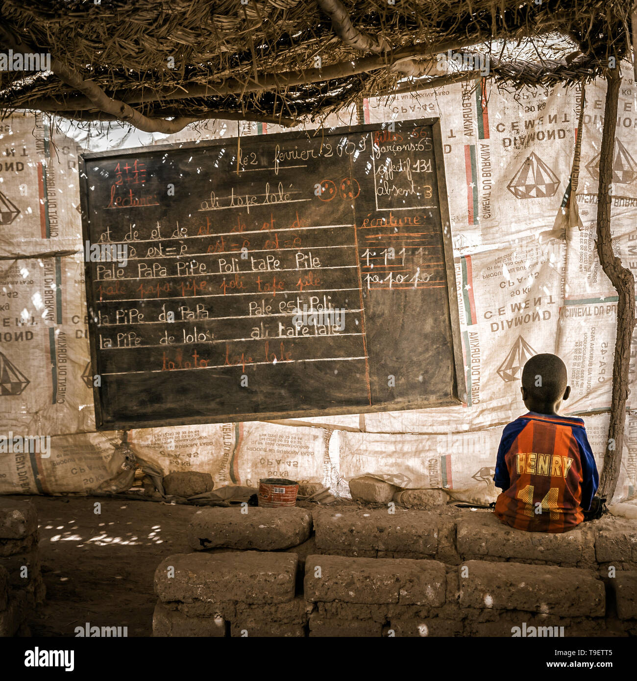 Young african kid alone in a classroom in the slums of Ouagadougou, Burkina Faso. Blackboard with french writings. Education in Africa concept. - Stock Image