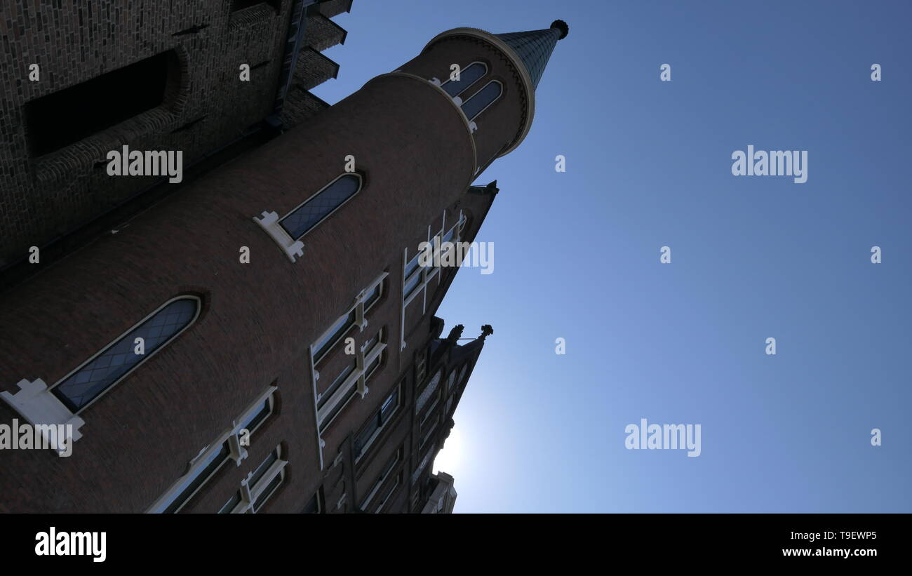 An old castle building photographed in a oblique position in the downtown in the Hague, The Netherlands - Stock Image