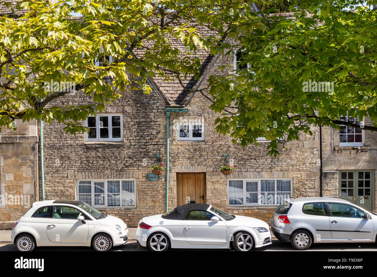 Old stone houses and new cars in the Market Place in the ancient Cotswold town of Northleach, Gloucestershire UK - Stock Image