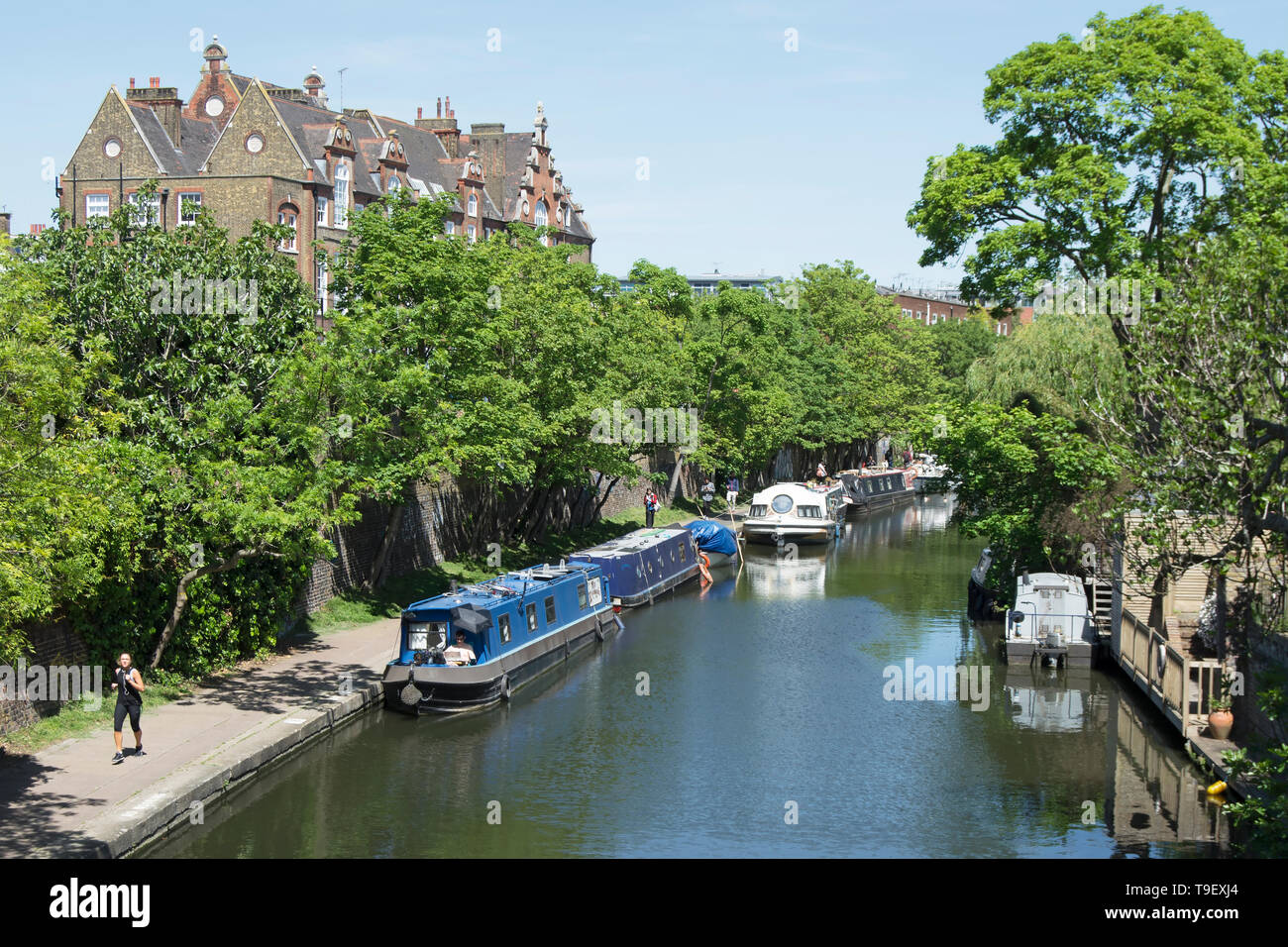 walkers and joggers on the towpath of regents canal looking towards camden town, london, england - Stock Image